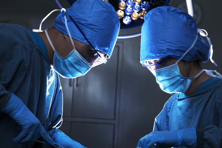 Two surgeons looking down, working, and concentrating at the operating table