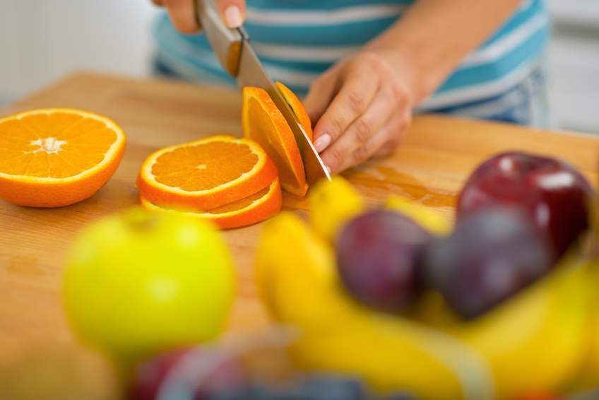 Closeup on young woman cutting orange